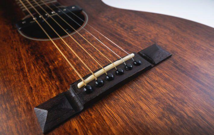 Acoustic guitar bridge of a brown instrument